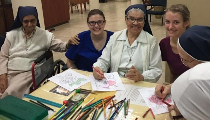 Davenport students coloring with several nuns at a community event.