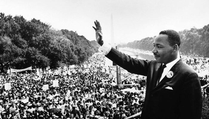Martin Luther King, Jr. waving to a crowd