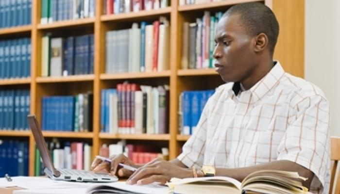picture of black male student studying in library