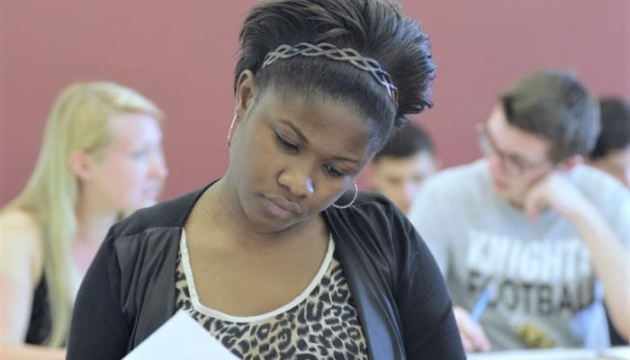 A Davenport student in a classroom looking at her textbook.